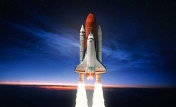 Space shuttle launch in the open space over the Earth. Sky and clouds under space ship. Elements of this image furnished by NASA