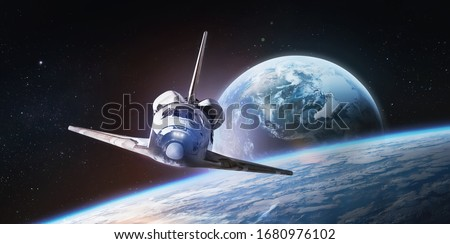 Space shuttle on orbit of the Earth planet. Spaceship. View from ISS. Elements of this image furnished by NASA.