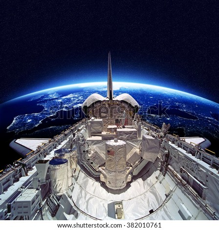 Stock Photo Space Shuttle orbiting the earth. Elements of this image furnished by NASA.