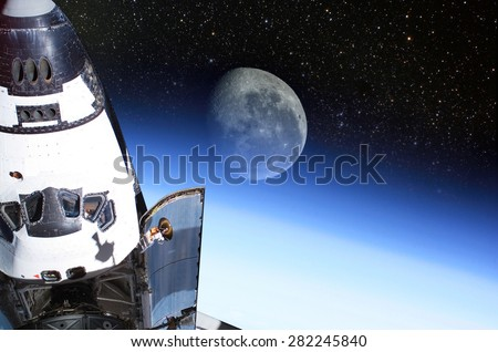 Space Shuttle orbiting the earth with moon background.\ Elements of this image furnished by NASA.
