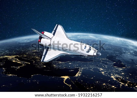 Space shuttle rocket flies over the blue planet earth with city lights on the background of stars. Spaceship launched into space start a mission and explore new planets Foto stock ©