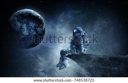 Spaceman on rock edge. Mixed media