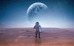 Spaceman on surface of red planet. Astronaut at space. Planet on background. Landscape of other world. Elements of this image furnished by NASA.