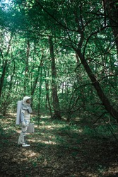 Spaceman wearing uniform is exploring a new place, standing among trees and holding small suitcase. Profile. Copy space on right side