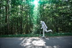 Spaceman wearing white armor is using scooter and driving through roar among trees. Profile. Copy space on left side