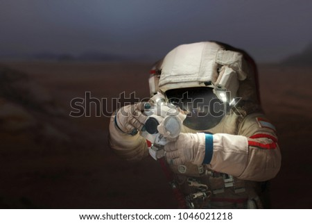 Spaceman with a camera in a space suit on the planet Mars. Astronaut takes pictures a new planet.