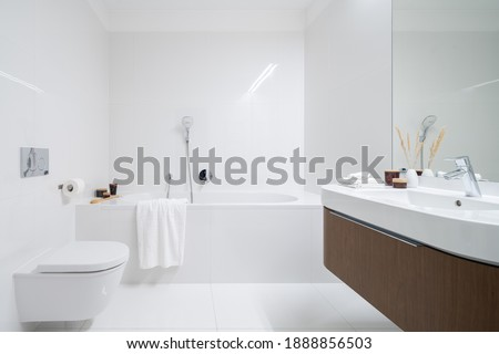 Spacious and elegant bathroom with big bathtub, white tiles, washbasin with wooden cabinet with drawer and big mirror Stock photo ©