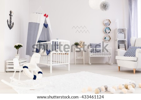 Spacious baby room with simple white furniture and beautiful marine decorations