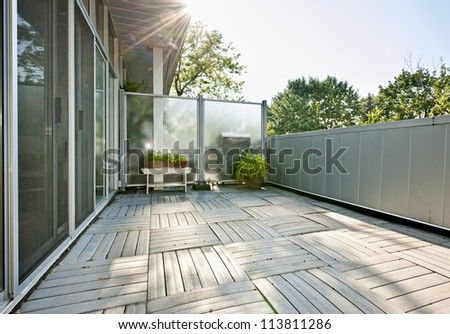 Spacious balcony of modern condo with plants on sunny day