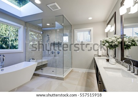Spacious bathroom in gray tones with heated floors, freestanding tub, walk-in shower, double sink vanity and skylights. Northwest, USA
