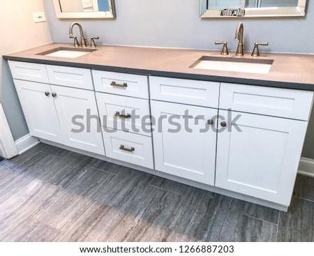 Spacious bathroom vanity counter top in gray tones with tile floors, white rectangular sinks, stainless steel mirrors, double handle chrome faucets and wooden white cabinets.