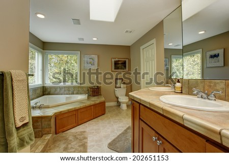 Spacious bathroom with tile wall trim and corner bath tub. View of ...