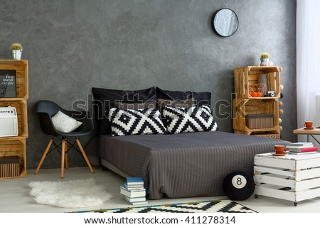 Spacious bedroom in grey, with handmade, wood furniture, big bed and decorative, pattern pillows