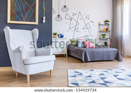 Spacious bedroom with bed and cosy armchair at the black wall background