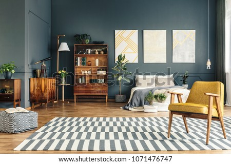 Spacious bright bedroom interior with armchair, plants, bed, pouf and bookshelves