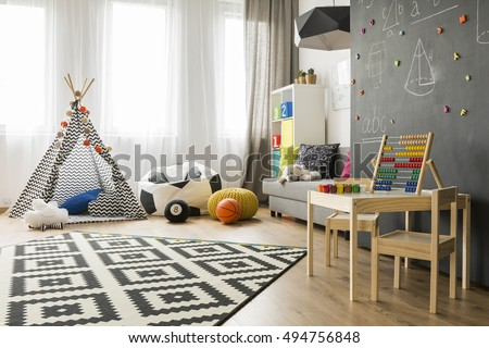 Spacious child room with window, play tent, sack chair, pattern carpet, regale, sofa, small table, chairs and blackboard wall