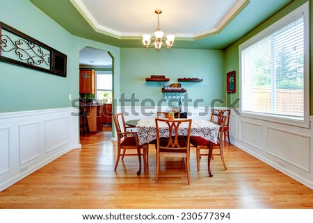 Spacious dining room in light mint color with white trim. Dining table set with crochet table cover and chairs