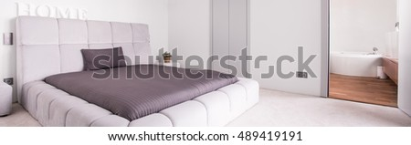 Spacious elegant bedroom and beige quilted bed #489419191