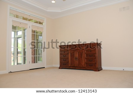 Spacious Empty Room - with only a dresser and a fan in the tray ceiling.  French doors lead to a covered porch.