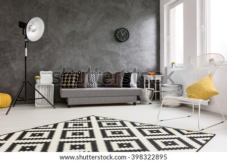 Spacious, grey living room with sofa, chair, modern standing lamp, small wood table and decorative carpet