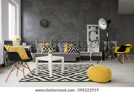 Spacious, grey living room with sofa, chairs, standing lamp, small coffee-table, decorations in yellow, black and white