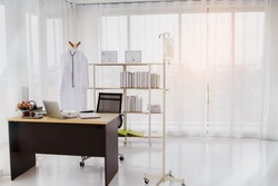 Spacious hospital doctor's office with clean aisles and convenient work equipment, Shelf decorated with diploma Medical