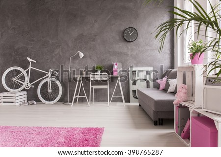 Spacious interior in grey and white with white bike, simple desk, chair and  sofa