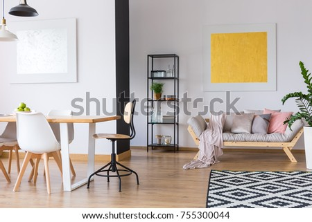 Spacious interior of a monochromatic day room with a carpet lying in front of a modern couch #755300044