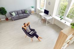 Spacious living room, study or office workspace with woman taking break from work on laptop. Modern interior of new apartment with large windows and person relaxing in comfortable armchair. High angle