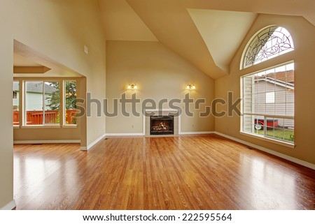 Spacious living room with high ceiling, big arch window, fireplace and new hardwood floor in empty new house