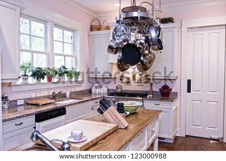 spacious modern kitchen with pot rack and island - stock photo