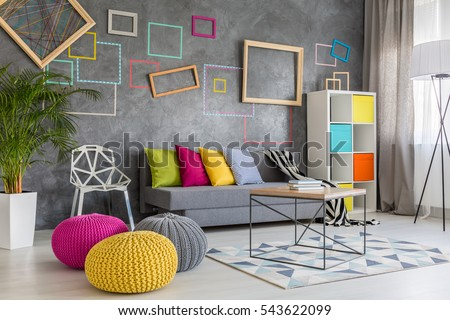 Spacious modern lounge with grey sofa and colorful pillows and poufs #543622099