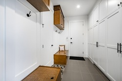 Spacious mud room with closets. benches and coat hooks