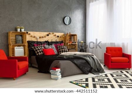 Spacious new bedroom decorated with style. Cozy double bed with wooden headboard red armchairs and wooden shelves #442511152