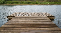 spacious pedestrian bridge made of wood on pontoons, easy boarding in boats