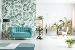 Spacious room with lamp next to blue couch against green wallpaper and pink chair near workspace