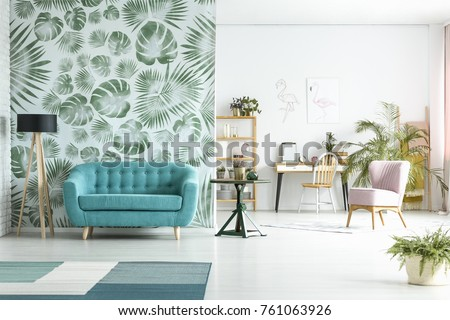 Spacious room with lamp next to blue couch against green wallpaper and pink chair near workspace #761063926