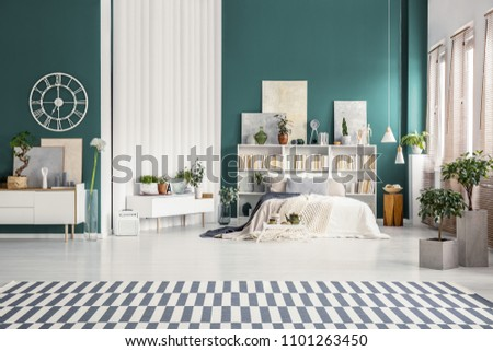Spacious studio apartment interior with turquoise green walls, white double bed and scandinavian furniture #1101263450
