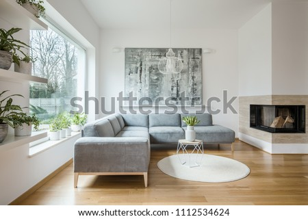 Spacious white living room interior with grey corner couch, big modern art painting and fireplace #1112534624