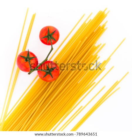 Spaghetti and cherry tomatoes isolated on white background. Uncooked Italian dried spaghetti. Top view. Flat lay.