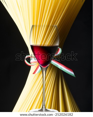 Spaghetti and glass of red wine with italian flag