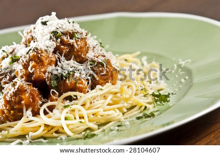 Spaghetti and meat balls with tomato sauce garnished with basil