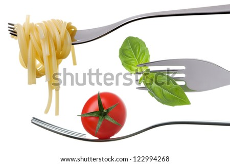 spaghetti basil and tomato on forks against a white background