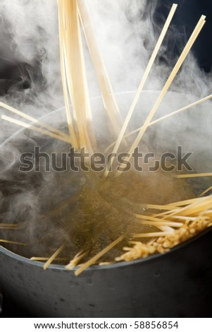 Spaghetti being cooked in hot water with steam making a dramatic image.