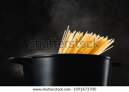 spaghetti boiling in black pan on dark background