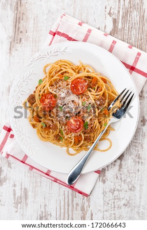 spaghetti bolognese on a plate on wooden table, top view, vertical