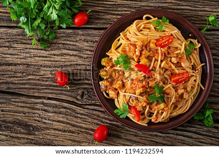 Stock Photo Spaghetti bolognese pasta with tomato sauce, vegetables and minced meat - homemade healthy italian pasta on rustic wooden background. Top view. Flat lay