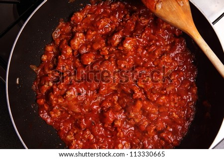 Spaghetti bolognese sauce being fried on a pan