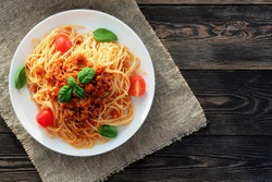 Spaghetti bolognese served on a white plate on a dark wooden background with tomatoes and basil