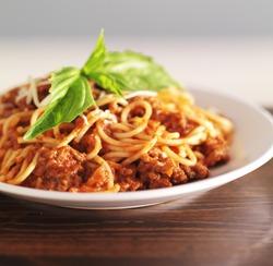 spaghetti bolognese with basil garnish